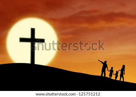 Silhouette of a Christian family walking toward Cross sign during sunset - stock photo