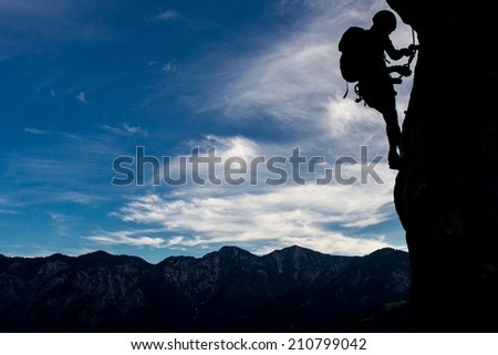 Silhouette of a climber high above mountains - stock photo