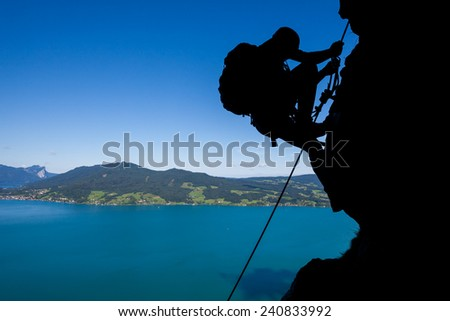 Silhouette of a climber high above the lake - stock photo