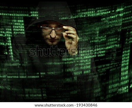 Silhouette of a computer hacker with binary codes from monitor - stock photo