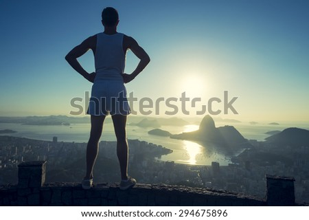 Silhouette of a confident athlete in white sport uniform standing with hands on hips in front of Rio de Janeiro Brazil sunrise skyline overlook at Sugarloaf Mountain - stock photo