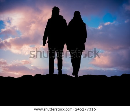Silhouette Of A Couple Hiking On A Mountain Against Beautiful Sunset - stock photo