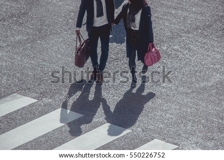 Silhouette of a couple hold hand across Pedestrians at Shibuya Junction, Tokyo, Japan
