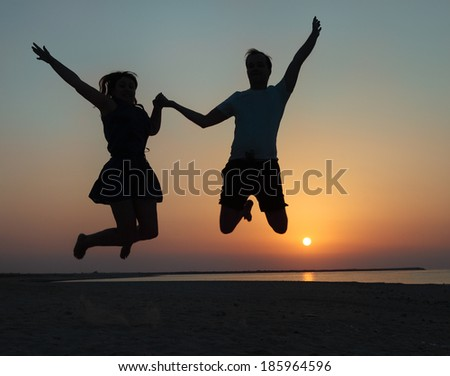 Silhouette of a couple - man and woman jumping on the beach at sunset  - stock photo