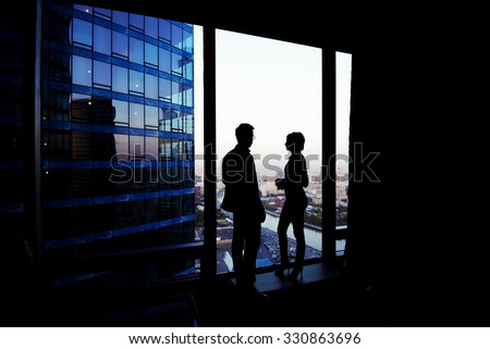 Silhouette of a couple of young business people having conversation while standing in hallway company near window, intelligent successful man and woman office workers discuss ideas during break - stock photo