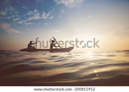 silhouette of a couple on a boat in the sea at sunset - stock photo