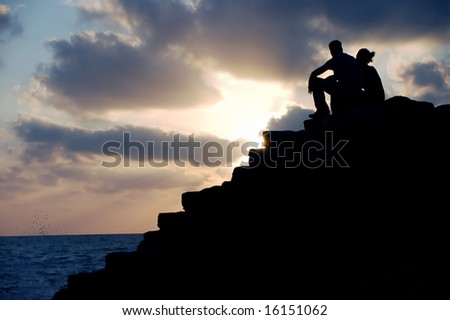 silhouette of a couple on sunset - stock photo