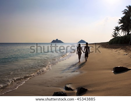 silhouette of a couple walking on a hawaii beach - stock photo