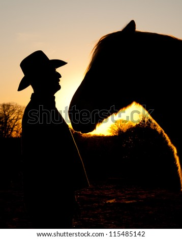 Silhouette of a cowboy and his big horse against sunset, face to face - stock photo
