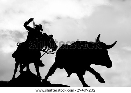 Silhouette of a cowboy statue riding down a bull.  This particular statue is found in a shopping center in Hawaii and is representative of the Hawaiian paniolos (cowboys).