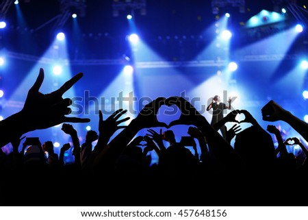 Silhouette of a crowd of cheering fans during a live concert, live music concert - stock photo
