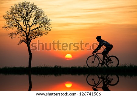 Silhouette of a cyclist at sunset - stock photo