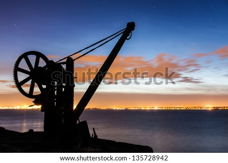 Silhouette of a davit in the evening with Dublin port backdrop