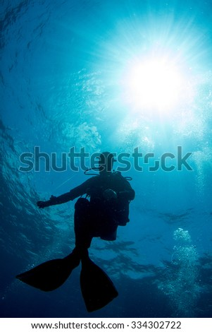 SIlhouette of a diver on the safety stop. Diver holding the buoy with the sun behind him through turquoise blue water.