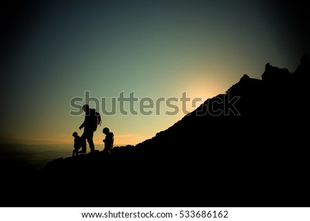 Silhouette of a family climbing a mountain while the sun is rising, children and Dad.