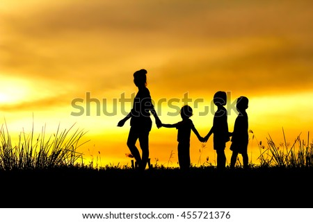 Silhouette of a family comprising a  mother and three children walking into the sunset.