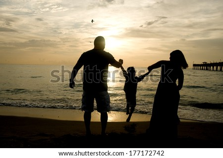 Silhouette of a family having fun at sunrise swinging their child
