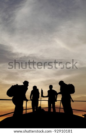 Silhouette of a family of backpacker tourists on an observation deck observing a dramatic surreal sunset. - stock photo