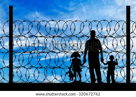 Silhouette of a family with children of refugees and fence with barbed wire on the background of the beautiful sky