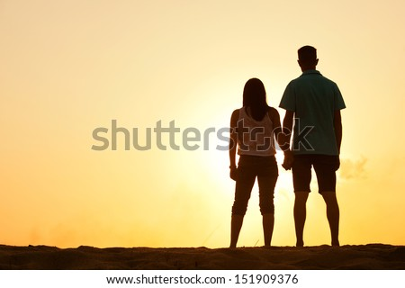 Silhouette of a female and male holding hands at sunset - stock photo