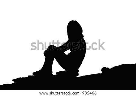 Silhouette of a Female sitting on a rocky slope - stock photo
