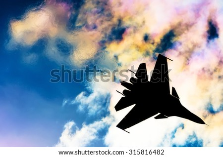 Silhouette of a fighter plane on a background of iridescent sky clouds and sun - stock photo