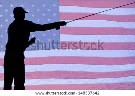 Silhouette of a Fisherman Holding a Fishing Pole fly fishing with a background of a USA American red white and blue flag.  - stock photo