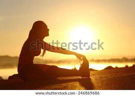 Silhouette of a fitness woman stretching at sunset with the sun in the background - stock photo