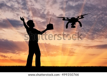 Silhouette of a flying drone, and a man with a remote control at sunset. Concept quadrocopters