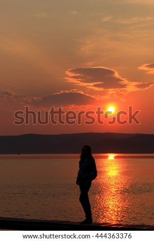 Silhouette of a girl against the sunset.