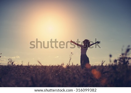 Silhouette of a girl enjoying sunset in the field (intentional sun glare and vintage color)