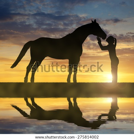 Silhouette of a girl giving a kiss horse in sunset - stock photo