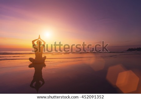 Silhouette of a girl in a pose of yoga on a beautiful sunset by the sea.