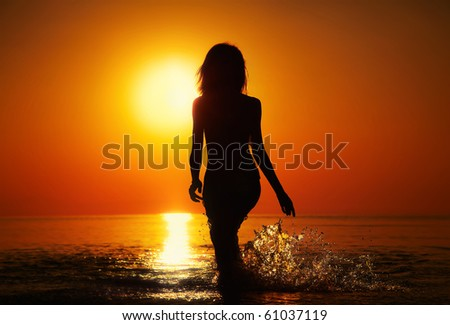 Silhouette of a girl in the water at sunset. Natural light and dark. Artistic colors added. Horizontal photo - stock photo