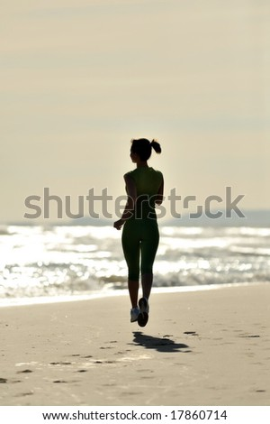 silhouette of a girl jogging on the beach at sunrise