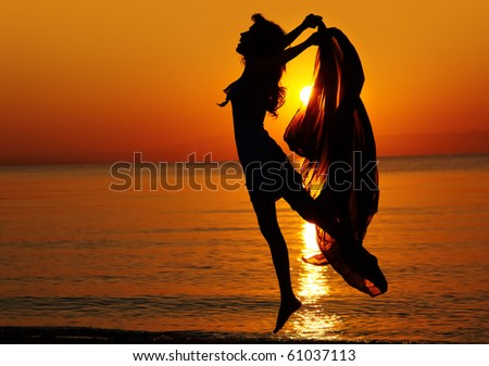 Silhouette of a girl jump down the beach at sunset. Natural light and dark. Artistic colors added. Horizontal photo