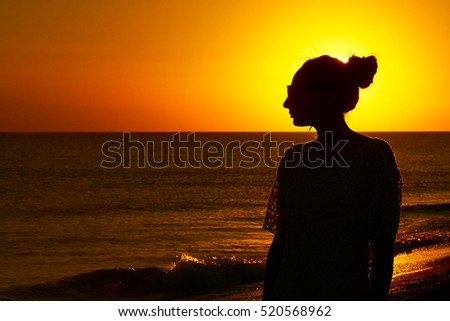 silhouette of a girl looking at the sunset on the sea