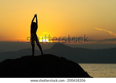 Silhouette of a girl on a background of mountains  - stock photo