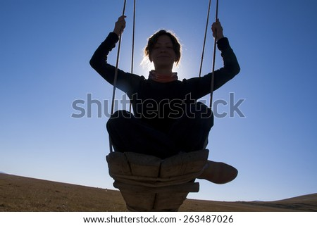 Silhouette of a girl on a swing - stock photo