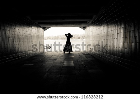 Silhouette of a girl on bright background at the end of an underground pedestrian tunnel - stock photo