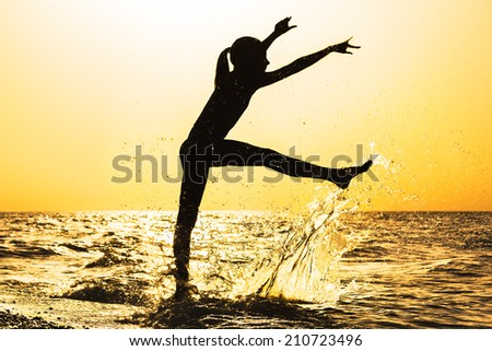 Silhouette of a girl splashing water on the beach at sunset