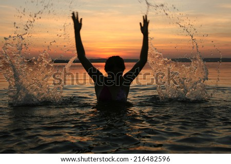 Silhouette of a girl spraying in lake at summer sunset cloudy sky background Face and hands of woman playing with splash of water Reflection on texture water - stock photo