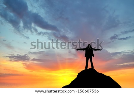 silhouette of a girl standing on a cliff side in his arms against the sunset - stock photo