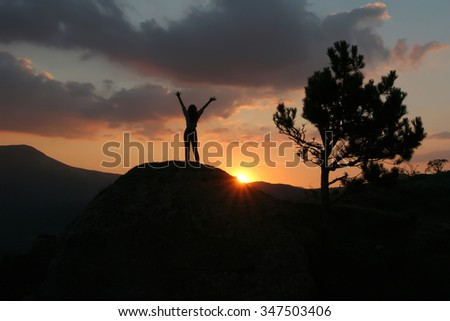 Silhouette of a girl standing on a mountain with his hands up against the setting sun. Girl standing in a pose rune man