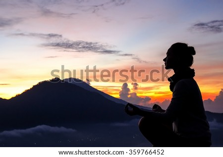 Silhouette of a girl that does yoga and meditation in the mountains at dawn. Stock image. - stock photo