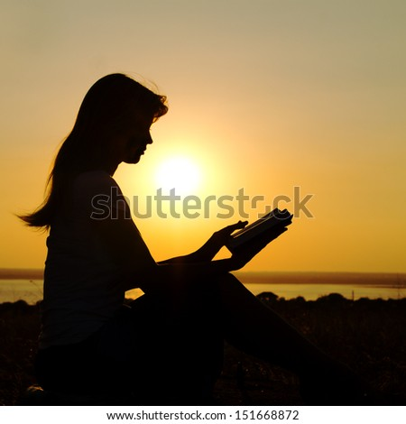 silhouette of a girl with a book in  hands at sunset - stock photo