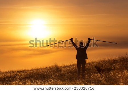Silhouette of a girl with sports Trekking pole in the morning mist with a loyal friend, a dog. Landscape composition, background mountains and sunrise. - stock photo
