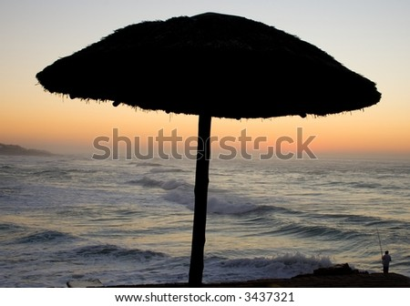 Silhouette of a grass umbrella with the sea in the background and the sun rising. - stock photo