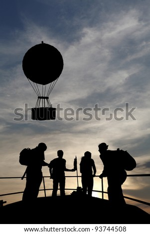 Silhouette of a group of backpacker tourists on the peak of an observation deck observing the silhouette of a hot air balloon floating against a dramatic surreal sunset.