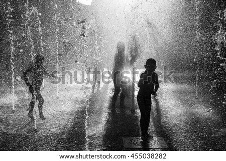 Silhouette of a group of happy children playing in a water fountain in the light of the setting sun